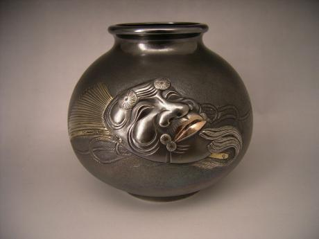 JAPANESE 20TH CENTURY SILVER VASE WITH OKINA NOH MASK DESIGN BY KOUSHUU<br><font color=red><b>SOLD</b></font>